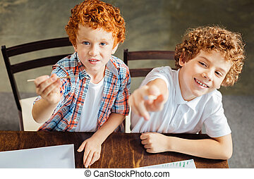 Little painters smiling into camera while painting together