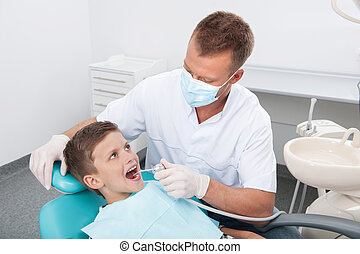 Little patient at dentist office. Top view of little boy sitting at the chair at the dental office while doctor examining teeth