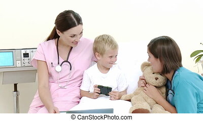 Little patient talking to a nurse and a pediatrician while...