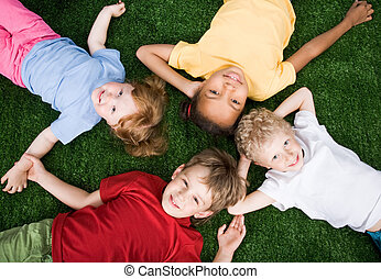 Little people - Team of little people lying on the grass ...