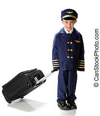 Little Pilot on the Go - A happy, kindergarten boy toting a ...