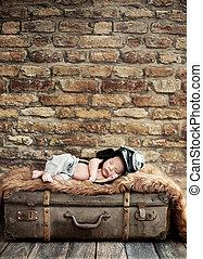 Little pilot sleeping on the suitcase