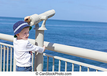 boy using seaside binoculars