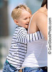 Little preschool boy playing and having fun outdoors with mother