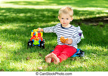 Little preschool boy playing with big toy car