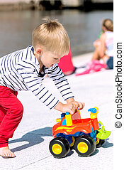 Little preschool boy playing with big toy car and having fun