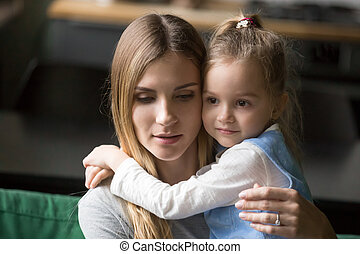 Little preschool girl embracing tired, upset mother
