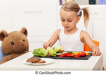 Little preschool girl having a healthy snack with her toy bear