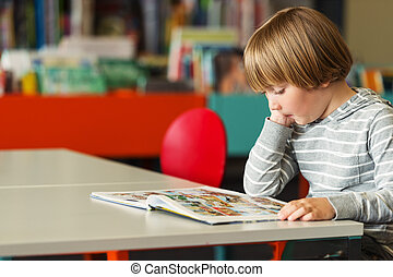Little preschooler boy of 5 years old reading book in the library