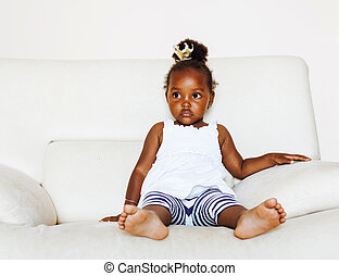 little pretty african american girl sitting in white chair weari