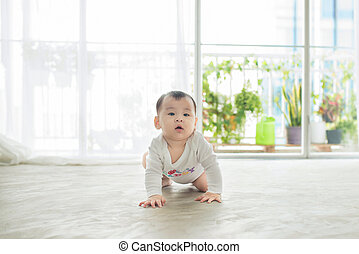 Little pretty baby girl crawling on the floor at home