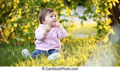 Little pretty baby-girl sitting on green grass in the park at the sunsat.