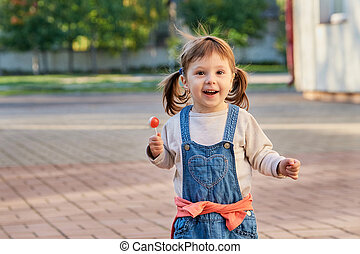 Little pretty girl eating candy in summer park. Adorable little girl in denim overalls smiling. Portrait of a child 2 years old, soft focus.