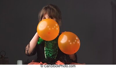 Little pretty girl in a beautiful dress inflating balloons orange color in turn with her mouth holding in her hands for the Halloween party. High quality 4k footage