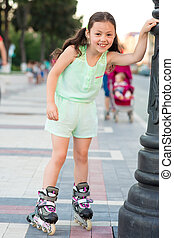 Little pretty girl on roller skates at a park