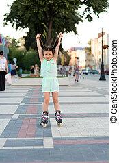 Little pretty girl on roller skates at a park