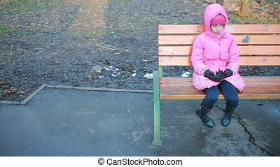 Little pretty girl sitting on a bench and sad at the park in autumn