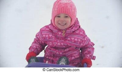Little pretty girl sledding in a winter park, winter family...