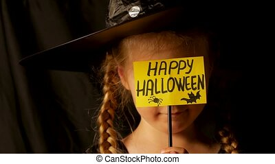 Little pretty girl witch in black wizard hat holds greeting Happy Halloween card says Boo and laughs. Child dressed in ghost party costume scarily staring at camera 4K festive autumn holiday footage.