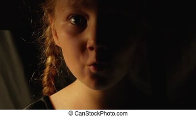 Little pretty girl witch in black wizard hat says Boo laughs. Smiling child dressed in ghost party costume funny staring at camera 4K festive greeting Happy Halloween holiday footage dark background.