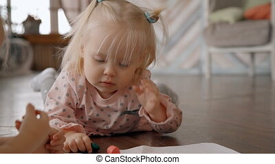 Little pretty girl with sweet pony tails is learning and practicing to draw by crayons. Charming blue eyes blonde is looking at her sister with curiosity and attentiveness and trying to copy her movements.