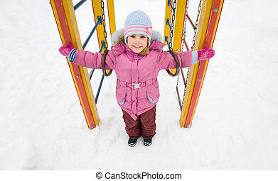 little pretty smiling girl in pink jacket on playground in winter, girl placed hands in sides