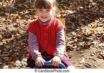 Little pretty smiling girl sits on wooden seesaw on playground at sunny day