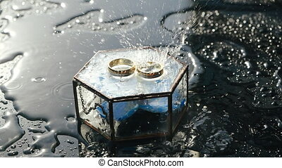 Little rain drips a smooth shiny surface of graphite color onto two gold wedding rings lying on a glass hexagon box with a chain in which there is a blue orchid flower. Rainy and sunny weather.