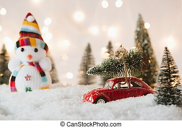 Little red car toy carrying Christmas tree