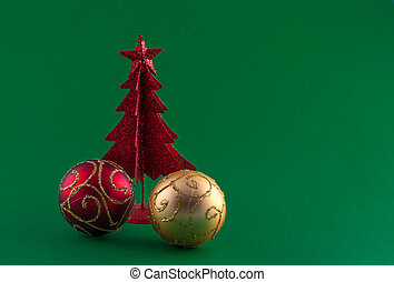 Little red christmas tree with tree adornments on green background