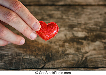 little red heart lies in the palms on a wooden background, the concept of love and romance.