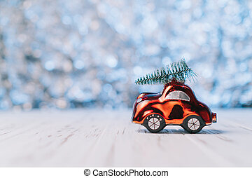Little red toy car carries a Christmas tree
