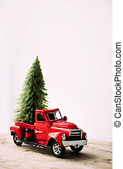 Little red toy car with green Christmas tree.