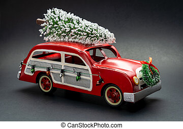 Little red vintage car carrying a Christmas tree on top