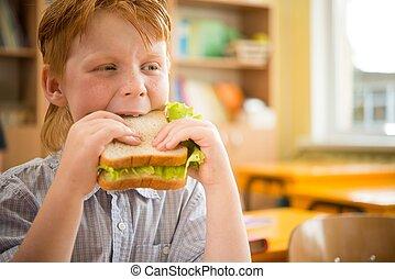 Little redhead schoolboy eating sandwich in class