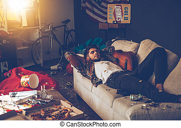 Little rest can help with hangover. Young handsome man lying down on sofa and napping in messy room after party