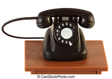 little retro black telephone on brown table isolated on white background