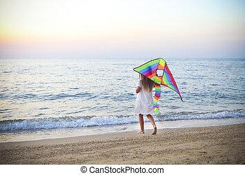 Little running girl with flying kite on beach at sunset