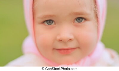 Little Russian girl posing in front of the camera. Smiling and looking close up. On the head is a pink headscarf.