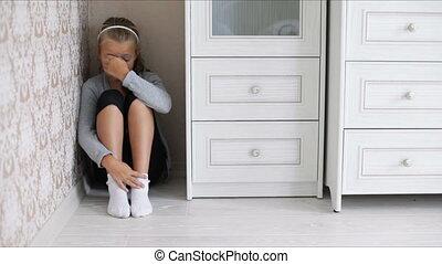 Little sad girl sitting on the floor