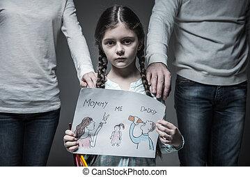 Little sad girl standing between her parents - My parents....