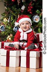 Little Santa boy sitting on a  gift boxes.