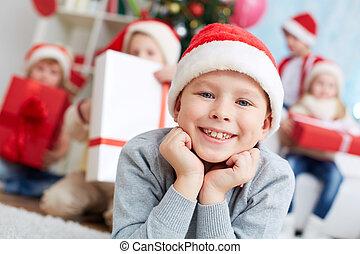 Little Santa - Image of cute lad in Santa cap looking at...