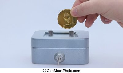 Little saving vault, hand holds golden Ethereum, ETH coin virtual money. Cryptocurrency, business and saving concept. High quality photo