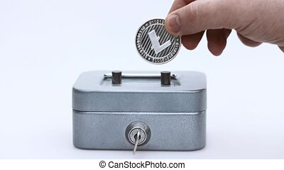 Little saving vault, hand holds silver LTC Litecoin virtual money. Cryptocurrency, business and saving concept. High quality photo