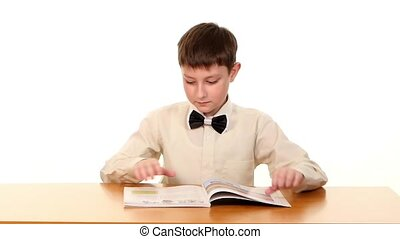 Little school boy looking for some information in the book, on white background, slow motion