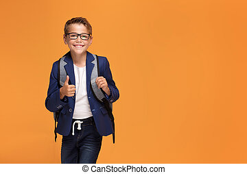 Little school boy with backpack smiling.