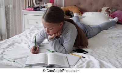 Little school girl lying on bed and doing homework