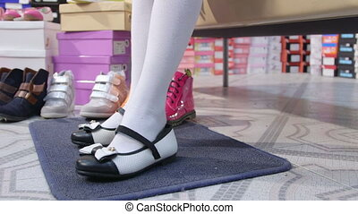 Little school girl trying on new black white flat shoes in children shoe store