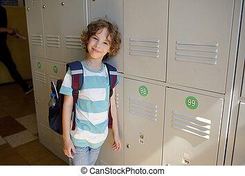 Little schoolboy standing near lockers in school hallway.
